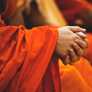 Orange robed clasped hands courtesy Peter Hershey at Unsplash